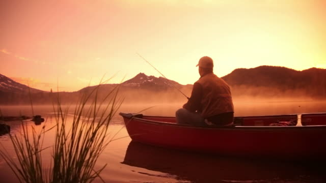 Man fishing in lake at sunrise video