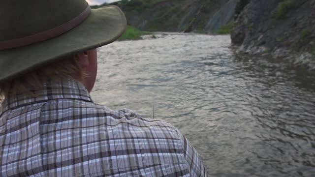 man fishing in river at sunset - solo un uomo maturo video stock e b–roll