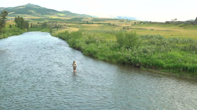 man fishing in river - solo un uomo maturo video stock e b–roll