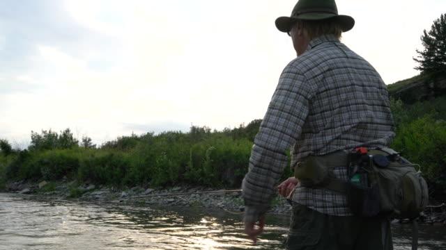 vidéos et rushes de homme de pêche dans la rivière - un seul homme d'âge mûr