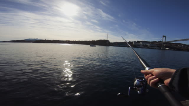 POV man fishing in the sea with a rod POV man fishing in the sea with a rod fishing rod stock videos & royalty-free footage