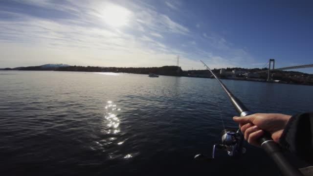 pov man fishing in the sea with a rod - łowić ryby filmów i materiałów b-roll