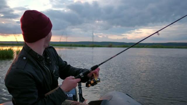 un uomo che pesca sul lago dalla barca al tramonto - acqua dolce video stock e b–roll