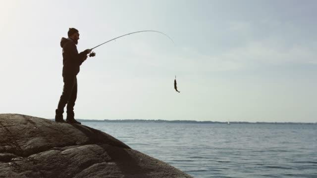 mann fischt mit einer rute von einem felsvorsprung - freizeitaktivität im freien stock-videos und b-roll-filmmaterial