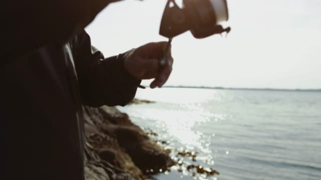man fishing with a rod from a rock spot - spranga video stock e b–roll