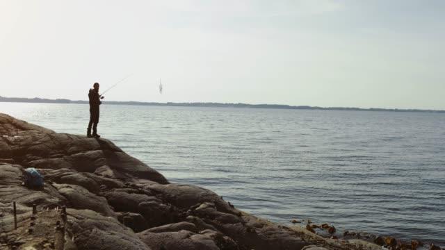 Mann fischt mit einer Rute von einem Felsvorsprung – Video