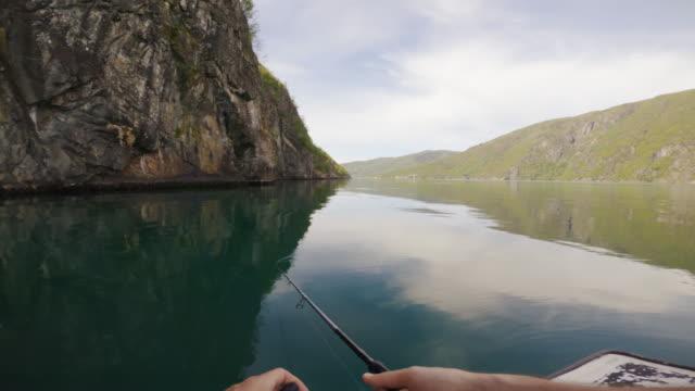 pov mann angeln mit einer rute von einem kleinen boot im meer an einem fjord, in norwegen - fang stock-videos und b-roll-filmmaterial