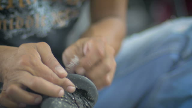 A man fixes a shoe by sanding off the old glue and roughens the rubber video
