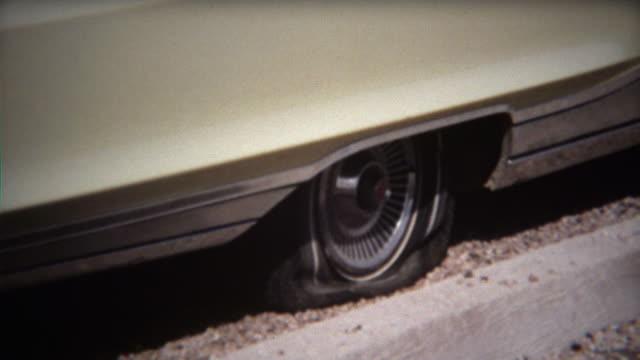 1971: Man fixes flat tire on white sedan car in hot sun.