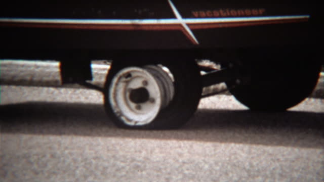 1971: Man fixing flat tire on camping trailer vacationeer vehicle.