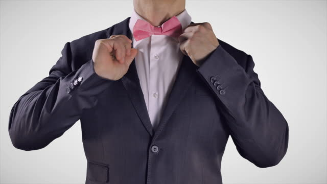 man fixing pink bow tie, white shirt, elegant tuxedo fashion suit - prom fashion stock videos and b-roll footage
