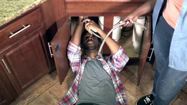 Man fixing pipe under kitchen sink