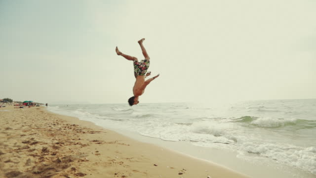 man flips and spins a sommersault on the beach - saltare video stock e b–roll