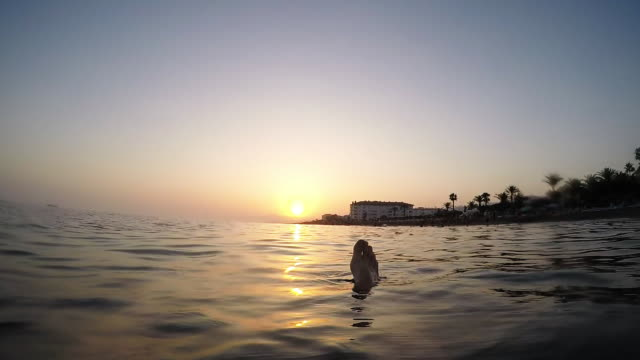 Man floating in a calm beach at sunset in slow - First person view - Loop
