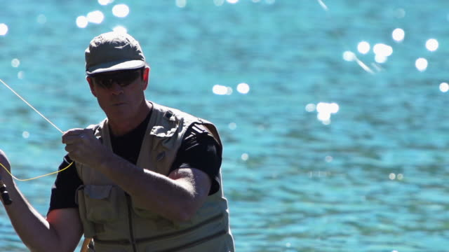 Hombre pesca con mosca en un lago de montaña - vídeo