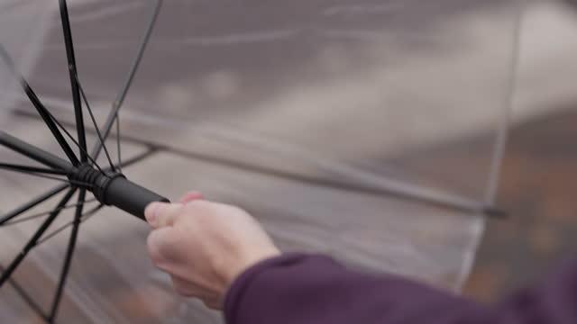 vídeos de stock e filmes b-roll de man folding out his umbrella - chapéu