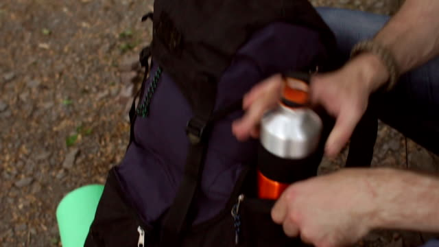 Man folding the water bottle in the backpack. Close-up of a tourist man is folding a bottle of water in his backpack. Close-up of the hands of men folding sports water bottle in a travel backpack. thirsty stock videos & royalty-free footage