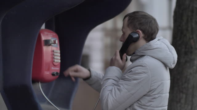 man from an russian calls frrom phone booth on the street in the autumn