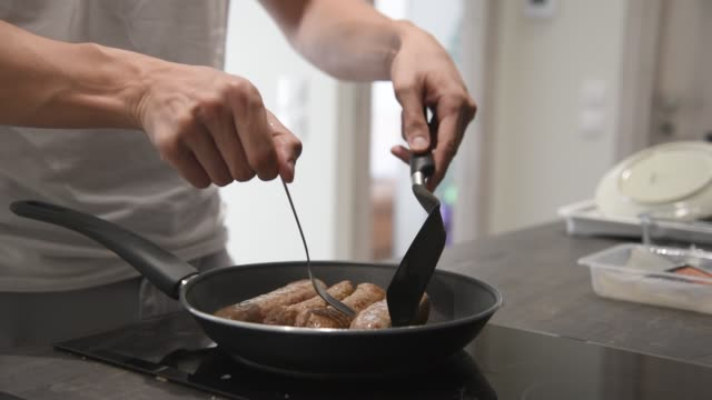 man frying meat in the kitchen. - articoli casalinghi video stock e b–roll