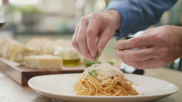 vidéos et rushes de homme garnissant les nouilles au basilic sur plaque à cuisine - parmesan