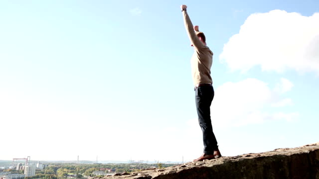 Man gesturing outside A happy man walking on a wall of stone outdoors, raising both his hands up in the air doing a victory sign. Its a sunny day with blue skys. macho stock videos & royalty-free footage