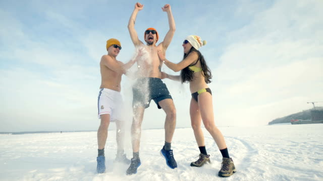 a man gets rubbed with snow by his laughing friends. 4k. - bikini video stock e b–roll