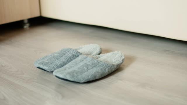 Un hombre obtiene en la cama y usa zapatillas - vídeo