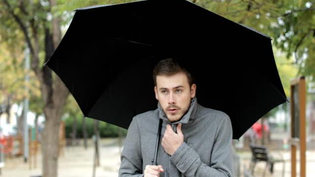 vídeos de stock e filmes b-roll de man getting cold in a rainy day walking in a park - pneumonia