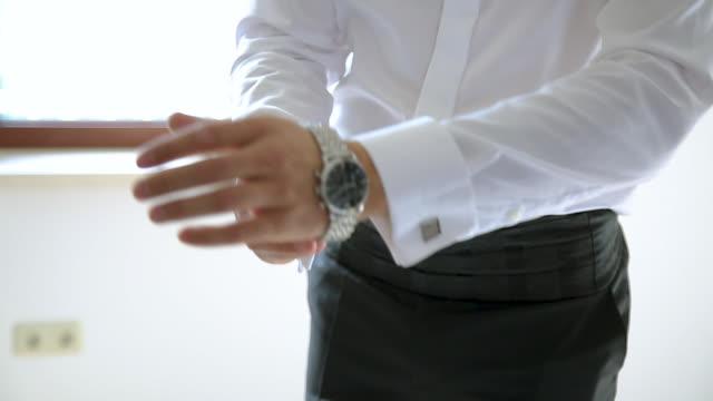 man getting dressed, putting wrist watch on his hand - dobrze ubrany filmów i materiałów b-roll