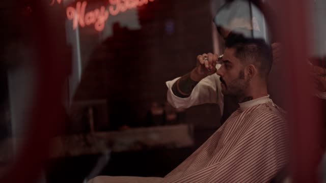 Man getting haircut by stylish barber in old-fashioned barber shop video