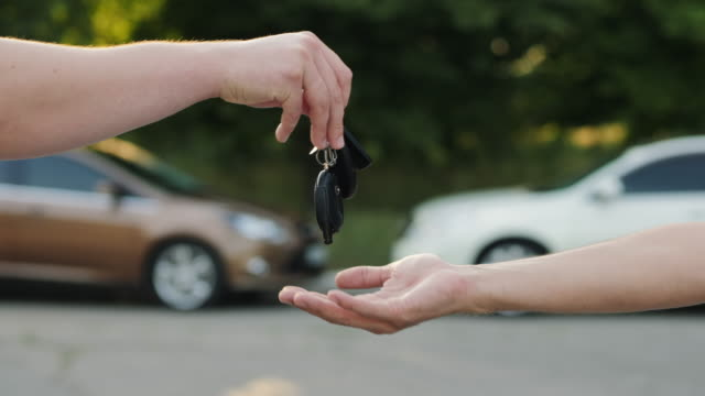 Man gives a car key to the other man