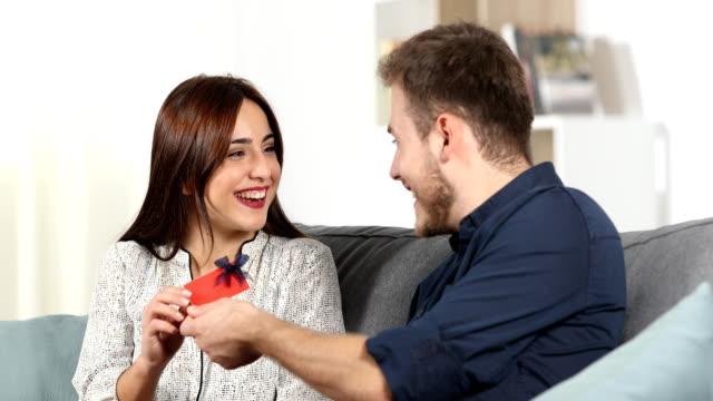 stockvideo's en b-roll-footage met man geeft een gift card aan zijn vriendin thuis - birthday gift voucher