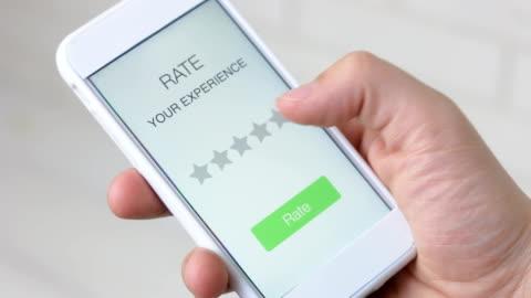 vídeos y material grabado en eventos de stock de hombre da cinco estrellas valorar mediante aplicación de smartphone - experto