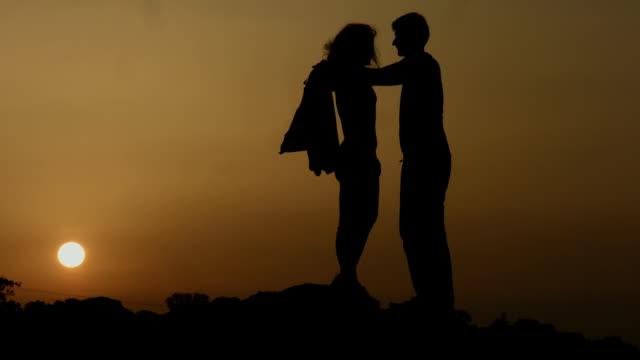человек дает жакет с любимой девушкой, показывает помощи в холодную погоду - жакет стоковые видео и кадры b-roll