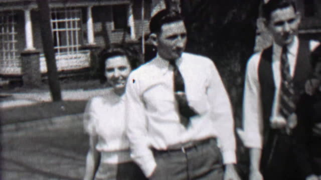 1939: Man gives women big hug for joining the family picture after all. video