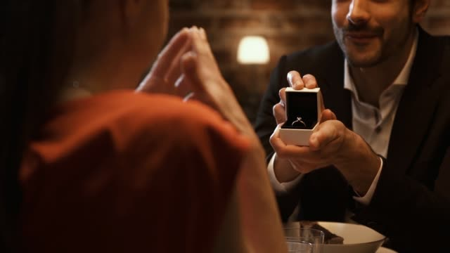 man giving an engagement ring to his girlfriend at the restaurant - помолвка стоковые видео и кадры b-roll