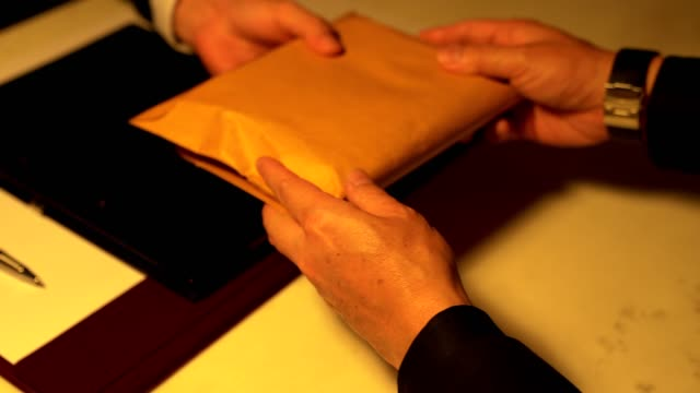 vídeos de stock e filmes b-roll de a man giving bribe money in a brown envelope to another businessman in a corruption scam - corruption