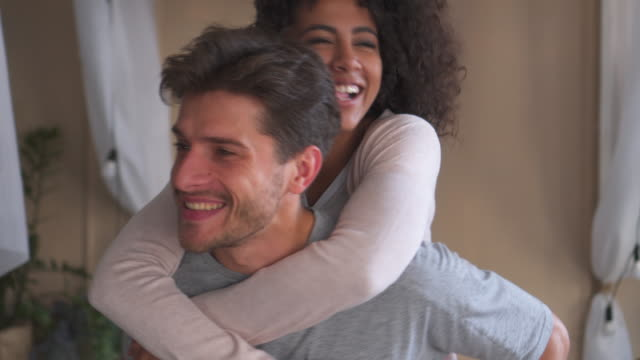 Man giving piggyback ride to woman at home video