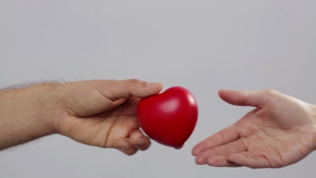 man giving red heart to woman