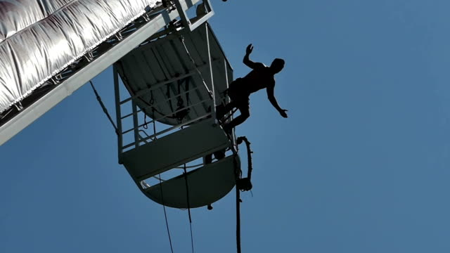 man goes bungee jumping-slow motion - bungee jumping video stock e b–roll
