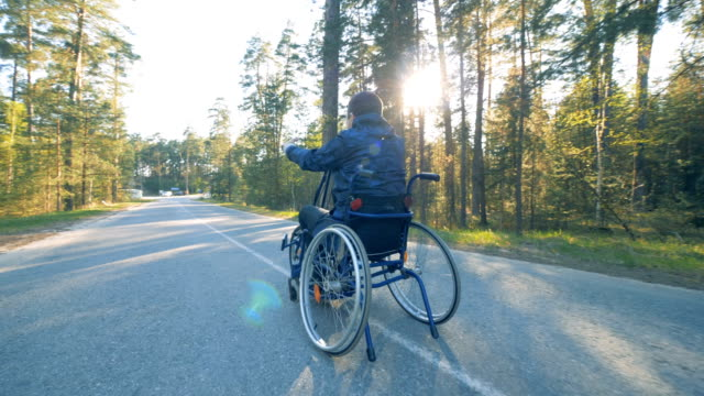 A man goes in a wheelchair, slow motion. A patient makes exercises on a bicycle with a wheelchair. wheelchair stock videos & royalty-free footage