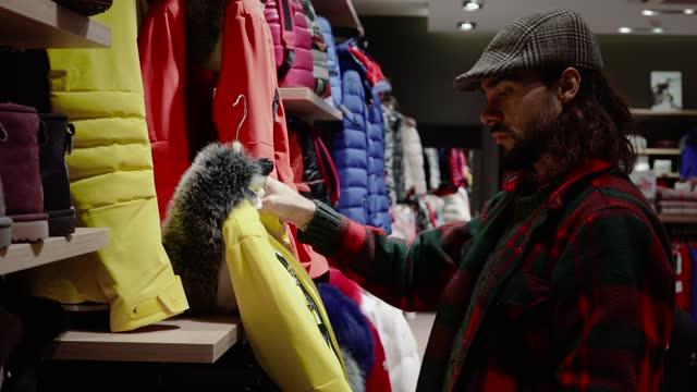 男は冬休みに買い物に行きます。私たちは冬服を見ることができます, 山でスキーに行くのに最適 - 近い景色4k - スポーツ用品点の映像素材/bロール