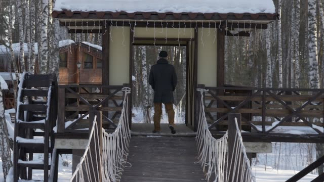 man going on the bridge and standing on wooden building - solo un uomo maturo video stock e b–roll