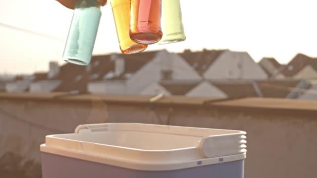 vidéos et rushes de homme en saisissant la boisson fraîche d'un refroidisseur au cours de la partie sur le toit - man drinking terrace