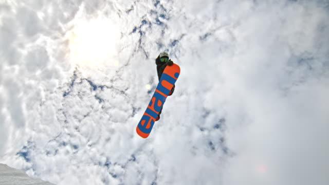 空中にジャンプしながら彼のスノーボードをつかんで slo mo 男 - 斜めから見た図点の映像素材/bロール