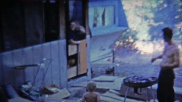 1973: Man grilling food outside trailer house for wife and baby.