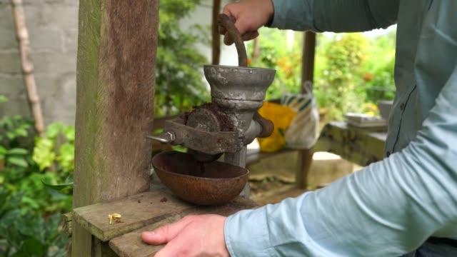 vídeos de stock e filmes b-roll de a man grinding cocoa beans with hand mill outdoors in cuba in 4k - cacau em pó