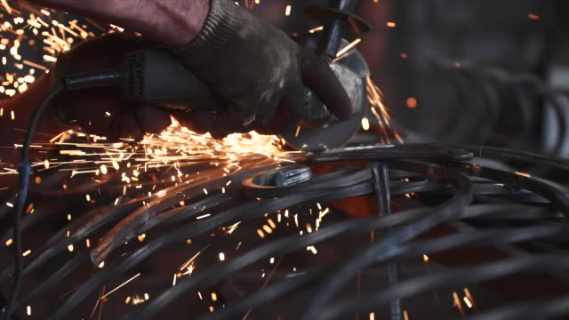 man grinds metal fence after welding using angle grinder in slow motion. - rettificatrice video stock e b–roll
