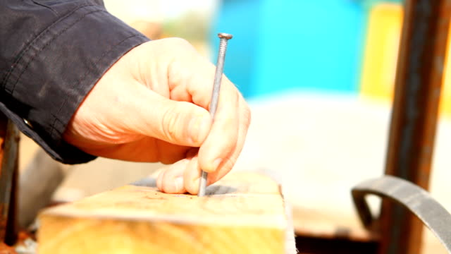 man hammers a nail into a plank video