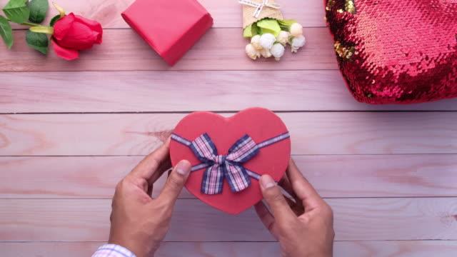 man hand ta hjärta form godis presentförpackning på bordet - recycling heart bildbanksvideor och videomaterial från bakom kulisserna
